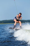 Slim brunette woman riding wakeboard on motorboat wave in lake Stock Photos