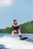 Slim brunette woman riding wakeboard on motorboat wave in lake Stock Photography