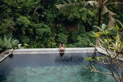 Slim brunette woman in swimsuit relaxing on edge infinity pool in jungle. Palms around and crystal clean water stock photos