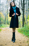 Slim brunette woman walking in a park Stock Images