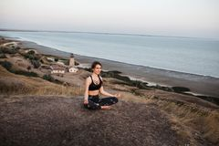 Slim brunette young girl Practicing Yoga in Lotus pose sitting on the edge of rock against of see and lighthouse stock photos
