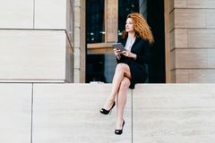 Slim businesswoman with wavy luxurious hair, having slender legs, wearing black elegant suit and shoes, holding tablet computer, l royalty free stock photos