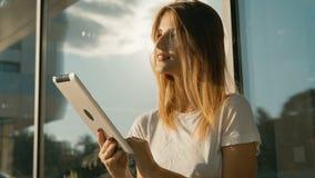 Girl Uses Tablet Before Modern Building. Slim caucasian girl, in white t-shirt, using a tablet before modern building , slowmotion in sunset stock video