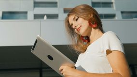 Girl Uses Tablet Before Modern Company. Slim caucasian girl, in white t-shirt, using a tablet before modern company, sunny day, slowmotion stock footage