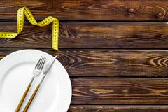 Slim concept with plate, flatware and measuring tape on wooden background top view mockup. Proper nutrition. Medical starvation. Slim concept with plate stock images