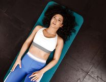 Slim curly dark-haired girl dressed in sports clothes doing exercises for the press on the mat for fitness in the gym royalty free stock images