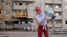 Slim cute beautiful young woman in construction helmet holds globe in her hands and adjustable wrench points to country or city