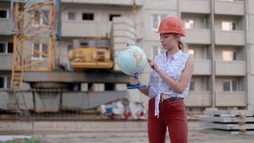 Slim cute pretty beautiful young woman in construction helmet holds globe in her hands, twists it and points to country or city