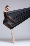 Slim dancer plays with black mesh fabric Stock Image