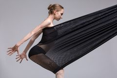 Slim dancer plays with black mesh fabric Royalty Free Stock Photos