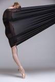 Slim dancer plays with black mesh fabric Stock Image