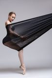 Slim dancer plays with black mesh fabric Stock Photography