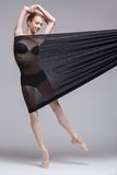 Slim dancer plays with black mesh fabric Stock Images