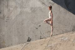Slim dancer stands in a ballet pose Stock Photos
