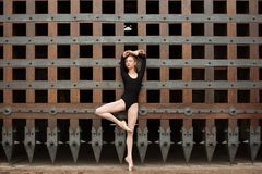 Slim dancer stands on one leg near the old gate Royalty Free Stock Image