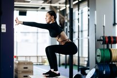 Slim dark-haired girl dressed in black sports clothes is doing squats on the box next to the sport equipment in the gym royalty free stock photos