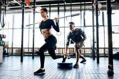 Slim dark-haired girl dressed in black sportswear is doing barbell squat and the coach helps her in the gym stock photo