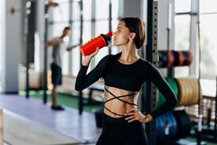 Slim dark-haired girl dressed in black sportswear drinks water in the gym near the sport equipment royalty free stock photos