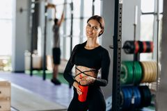 Slim dark-haired girl dressed in black sportswear stands with water in her hand near the sport equipment in the gym stock photography