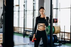 Slim dark-haired girl dressed in black sportswear stands with water in her hand near the sport equipment in the gym royalty free stock photo
