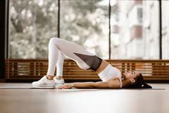 Slim dark-haired girl dressed in white sports clothes has a work out on the mat for fitness in the gym stock photos