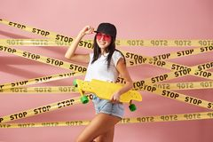 Slim dark-haired girl in pink sunglasses and cap dressed in jeans shorts and white top stands with yellow skateboard on royalty free stock photos
