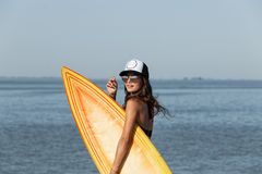 Slim dark-haired girl in sunglasses and cap dressed in a black bra and jean shorts is standing near the sea and holding stock photo