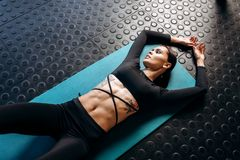 Slim dark-haired girl with tattoo dressed in black sports clothes is lying on the mat for fitness in the gym stock photo