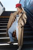 Slim dark-haired model wearing baggy jeans and beige trench coat. Baggy jeans. Slim dark-haired young model wearing baggy jeans and beige trench coat stock images