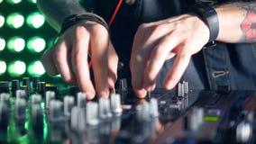 Slim DJs hands manipulate mixer console settings. stock footage