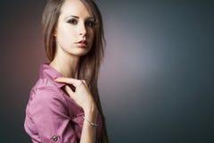 Slim fashion model posing on dark background. Stock Images