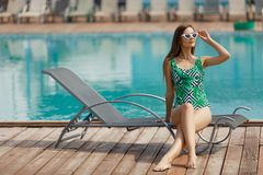 Slim fashion model in a swimsuit posing near the pool Stock Images