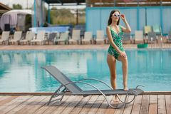 Slim fashion model in a swimsuit posing near the pool Stock Photos