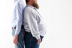 Slim and fat guys posing. Real opposites. Close up side view of body of two thin and thick men. is standing with large belly and beard. Isolated and copy space royalty free stock photo
