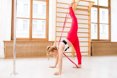 Acrobatics. Slim female in activewear practicing yoga exercises or acrobatics with resistance band royalty free stock photography