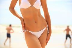 Slim female body in bikini and guys playing fresbee. On the beach Stock Images
