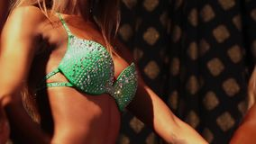 Slim female bodybuilder posing in bikini, fitness competition stock footage