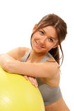 Slim female fitness instructor with ball in gym Royalty Free Stock Image
