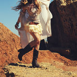 Slim female legs dressed in leather cowboy shoes with short lace skirt, fashion woman. Dancing on a rocks Stock Photo