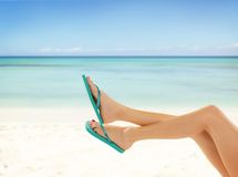 Slim female legs on sandy beach Stock Photo