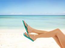 Slim female legs on sandy beach Stock Photo
