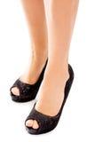 Slim female legs wearing black high heels royalty free stock photo