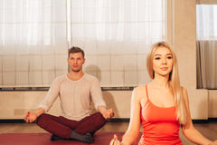 Slim female and man on background meditating in pose of lotus in gym Stock Photo
