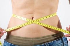 Slim female measuring her waist Royalty Free Stock Photos