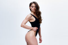 Slim female model in a black bodysuit on the white background Stock Image