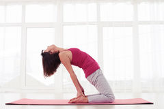 Slim female practices ustrasana or camel pose Royalty Free Stock Photos