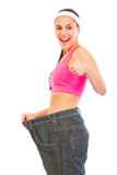 Slim female pulling oversized jeans Royalty Free Stock Image