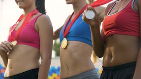 Slim female winners showing their medals, posing for photos at awarding ceremony
