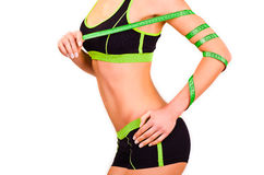 Slim figure of girl with a centimetre ribbon on a hand. Slim figure of girl is in a sportwear with a centimetre ribbon on a hand Royalty Free Stock Images