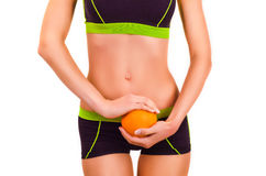Slim figure of girl with orange in a hands. Slim figure of girl in a sportwear with orange in a hands Stock Photography